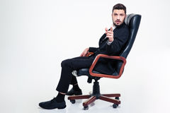 Thoughtful handsome business man in office chair pointing on you. Thoughtful handsome young business man with beard in black suit in black office chair pointing Royalty Free Stock Photos