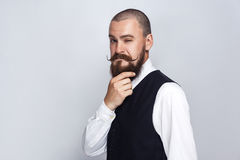 Thoughtful, Handsome businessman with beard and handlebar mustache looking at camera and thinking. Studio shot, on gray background royalty free stock photo