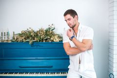 Thoughtful, handsome man with a beard in white clothes against the background of a piano, a rasped shirt with a bare torso. Thoughtful, handsome man with a beard Royalty Free Stock Photo