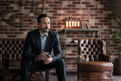 Thoughtful handsome man drinking whisky. Drinking alcohol. Pleasant handsome thoughtful man holding a glass and drinking whisky while sitting on the table Royalty Free Stock Images