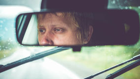 Thoughtful handsome man riding in car through mountains during rainy day. Sad, thoughtful man riding in car through mountains during rainy day Royalty Free Stock Photography