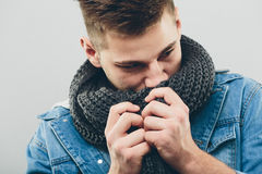 Thoughtful Handsome Man Smelling his Knitted Scarf. Close up Serious Handsome Young Man Wearing Denim Jacket, Thinking of Something While Smelling his Gray Stock Images