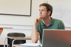 Thoughtful handsome mature student sitting in classroom while learning Royalty Free Stock Photography
