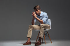 Thoughtful handsome young man sitting on chair and looking away stock photos
