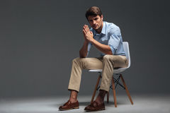 Thoughtful handsome young man sitting on chair and looking camera royalty free stock images