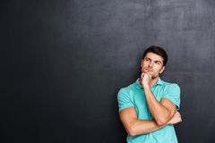 Thoughtful handsome young man standing and thinking. Over chalkboard background Royalty Free Stock Photography