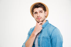 Thoughtful handsome young man standing and thinking Stock Photo