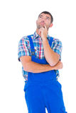 Thoughtful handyman in coveralls looking up Royalty Free Stock Image