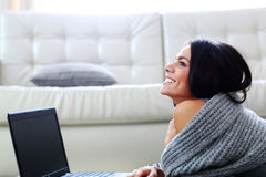 Thoughtful happy woman lying on the floor with laptop Stock Photo