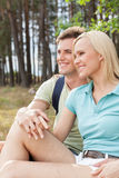 Thoughtful hiking couple looking away while relaxing in forest Stock Photography