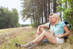 Thoughtful hiking couple looking away while relaxing in forest Stock Photo