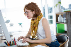 Thoughtful hipster businesswoman concentrating on her computer Stock Photos