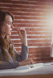 Thoughtful hipster businesswoman watching computer Royalty Free Stock Image
