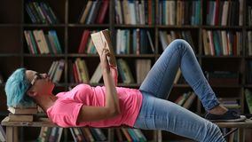 Pensive female hipster reading a book in library. Thoughtful hipster girl with blue hair and eyeglasses lying on her back on the bench and reading a book at stock footage