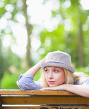 Thoughtful hipster girl sitting on bench in the park Stock Photo