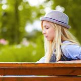 Thoughtful hipster girl sitting on bench in park Stock Image