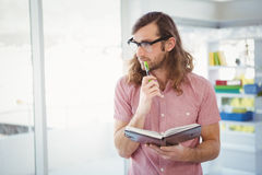 Thoughtful hipster holding pen and book Royalty Free Stock Images