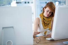 Thoughtful hipster woman looking at colour swatches Stock Photo
