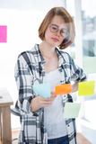 Thoughtful hipster woman reading some post it notes. Thoughtful hipster woman, sitting at her desk reading notes Royalty Free Stock Photo