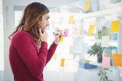 Thoughtful Hipster writing on sticky note Stock Image