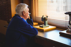 Thoughtful horologist looking through window Royalty Free Stock Photo