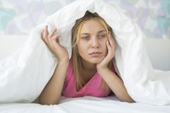 Thoughtful ill woman covered with quilt in bed Stock Photography