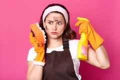 Thoughtful impressed housewife looks at dirty sponge, looks shocked, posing  over pink background in studio. Exhausted. Brunette female wears brown apron, white stock photos