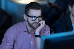 Thoughtful intelligent programmer concentrating on his job. Involved in work. Thoughtful intelligent smart men holding his chin and looking at the computer Stock Image