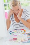 Thoughtful interior designer looking at a colour wheel Stock Photography
