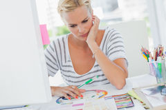 Thoughtful interior designer looking at colour wheel. On her desk with colour charts Royalty Free Stock Photo