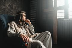 Thoughtful Jesus Christ sitting in a chair. Thoughtful man in the image of Jesus Christ sitting in a chair against window with crucifixion cross. Hard times for Royalty Free Stock Photography