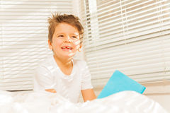 Thoughtful kid boy sitting in his bed with a book Royalty Free Stock Photo