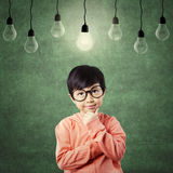 Thoughtful kid with casual clothes under light bulb Stock Image