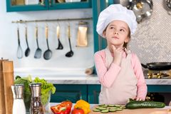 thoughtful kid in chef hat and apron looking away stock photography