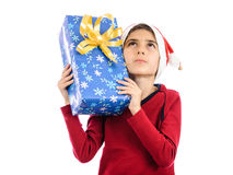 Thoughtful kid with Christmas present looking up Royalty Free Stock Photo