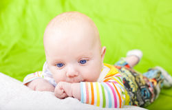 The thoughtful kid lies on a pillow. Royalty Free Stock Photography
