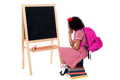 Thoughtful kid sitting in front of blackboard Royalty Free Stock Photos