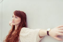Thoughtful Lady Leaning on Wall with Open Arms. Close up Thoughtful Young Attractive Lady with Brown Wavy Hair, Leaning on the White Wall with Wide Open Arms and Royalty Free Stock Photography