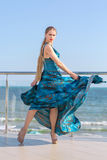 A thoughtful lady in a long dark blue dress on the ocean background. The woman in a long flowing dress on a hotel terrace. royalty free stock images
