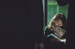Thoughtful lady reading while traveling by train Stock Photos