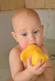 Thoughtful little baby is bathed in the bath with duck Royalty Free Stock Photography