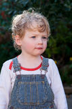 Thoughtful little boy in coveralls Royalty Free Stock Photos