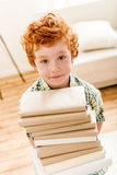 Thoughtful little boy holding pile of books Royalty Free Stock Image