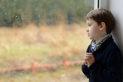 Thoughtful little boy looking through the window. Royalty Free Stock Photography