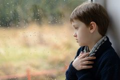 Thoughtful little boy looking through the window. Royalty Free Stock Images