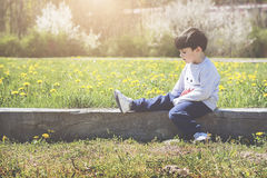 Thoughtful little boy. Sitting on field Royalty Free Stock Images