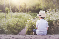 Thoughtful little boy sitting on field. Thoughtful child with hat sitting in the field Royalty Free Stock Images