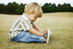 A thoughtful little boy sitting on the grass in a Stock Photo
