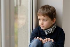 Thoughtful little boy sitting on the windowsill Stock Photo