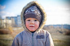 Thoughtful little boy on walk in the autumn. The thoughtful little boy on walk in the autumn in a hood on the nature Royalty Free Stock Image